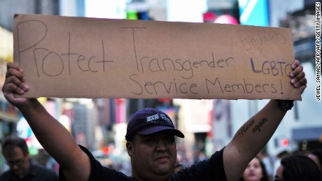 "A protester displays a placard during a demonstration against US President Donald Trump, in front of the US Army career center in Times Square, New York, on July 26, 2017.  Trump announced on July 26 that transgender people may not serve ""in any capacity"" in the US military, citing the ""tremendous medical costs and disruption"" their presence would cause. / AFP PHOTO / Jewel SAMAD        (Photo credit should read JEWEL SAMAD/AFP/Getty Images)"