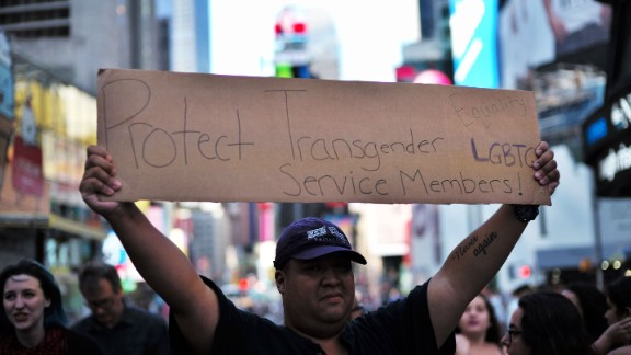 "A protester displays a placard during a demonstration against US President Donald Trump, in front of the US Army career center in Times Square, New York, on July 26, 2017.  Trump announced on July 26 that transgender people may not serve ""in any capacity"" in the US military, citing the ""tremendous medical costs and disruption"" their presence would cause. / AFP PHOTO / Jewel SAMAD"