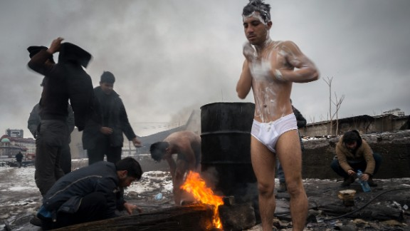 Migrants bathe outside near a makeshift shelter in an abandoned warehouse in Subotica, Serbia, in January 2017.