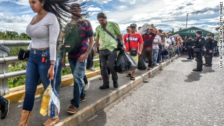 TOPSHOT - Venezuelan citizens cross the Simon Bolivar international bridge from San Antonio del Tachira, Venezuela to Cucuta, Norte de Santander Department, Colombia, on July 25, 2017. Some 25.000 Venezuelans cross to Colombia and return to their country daily with food, consumables and money from ilegal work, according to official sources. Also, there are 47.000 Venezuelans in Colombia with legal migratory status and another 150.000 who have already completed the 90 allowed days and are now without visa.  / AFP PHOTO / Luis Acosta        (Photo credit should read LUIS ACOSTA/AFP/Getty Images)