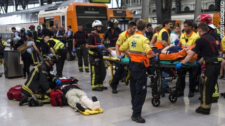Spanish firefighters and paramedics treat injured people.