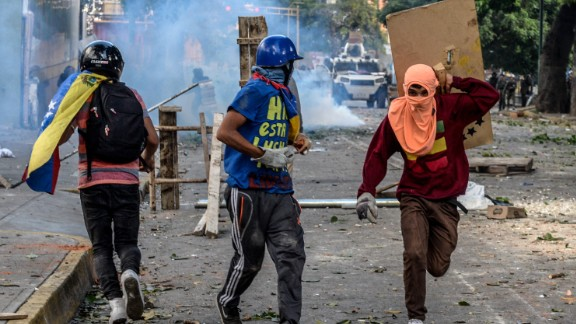 Masked opposition demonstrators take part in clashes with riot police ensuing an anti-government protest in Caracas, on July 26, 2017. Venezuelans blocked off deserted streets Wednesday as a 48-hour opposition-led general strike aimed at thwarting embattled President Nicolas Maduro