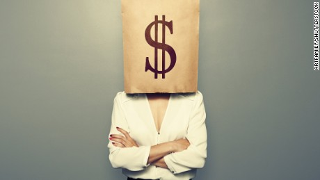 businesswoman hiding under paper bag with dollar sign over dark background; Shutterstock ID 193696625