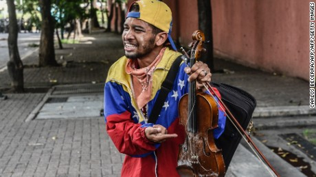 Opposition activist  Wuilly Arteaga shows his broken violin during a protest in Caracas, on May 24, 2017. Venezuela's President Nicolas Maduro formally launched moves to rewrite the constitution on Tuesday, defying opponents who accuse him of clinging to power in a political crisis that has prompted deadly unrest. / AFP PHOTO / CARLOS BECERRA        (Photo credit should read CARLOS BECERRA/AFP/Getty Images)