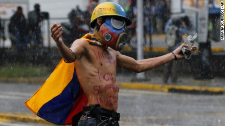 A protester faces off against national guard troops as clashes continued Friday in Caracas despite rain.
