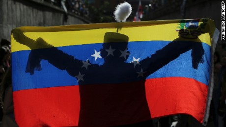 In this Monday, July 24, 2017 photo, a demonstrator dressed as Venezuelan independence hero Simon Bolivar is silhouetted against a national flag during a tribute to those killed in the recent wave of anti-government protests, in Caracas, Venezuela. The most recent violence drove the death toll from nearly four months of unrest above 100 Thursday, July 27. Most of the dead in anti-government protests that began in early April have been young men killed by gunfire.