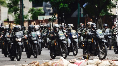 National Guard motorcyclists in riot gear charge on opposition activists blocking an avenue protesting against the election of a Constituent Assembly, in Caracas on July 30, 2017. Deadly violence erupted around the controversial vote, with a candidate to the all-powerful body being elected shot dead and troops firing weapons to clear protesters in Caracas and elsewhere. / AFP PHOTO / RONALDO SCHEMIDT        (Photo credit should read RONALDO SCHEMIDT/AFP/Getty Images)