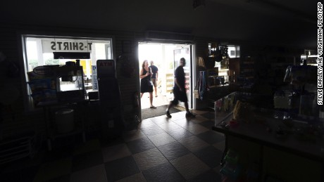 Customers enter the darkened Island Convenience Store in Rodanthe on Hatteras Island on Friday, July 28, 2017. Non-residents were asked to evacuate the island and neighboring Ocracoke Island due to a loss of electrical power.