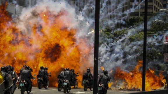 Members of Venezuela's national police are caught in an explosion as they ride motorcycles near Altamira Square in Caracas on July 30. Venezuela has seen widespread unrest since March 29, when the Supreme Court dissolved Parliament and transferred all legislative powers to itself. The decision was later reversed, but protests have co