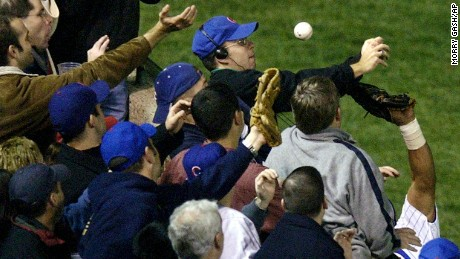 On October 14, 2003, Cubs left fielder Moises Alou's arm reaches into the stands unsuccessfully for a foul ball tipped by fan Steve Bartman, wearing headphones and glasses.