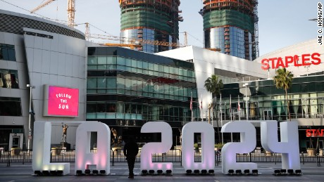 "FILE- In this Thursday, May 11, 2017 file photo, a Los Angeles 2024 sign stands in front of Staples Center, in Los Angeles. An International Olympic Committee panel has praised Los Angeles and Paris for ""outstanding"" plans to host the 2024 Summer Games. (AP Photo/Jae C. Hong, File)"