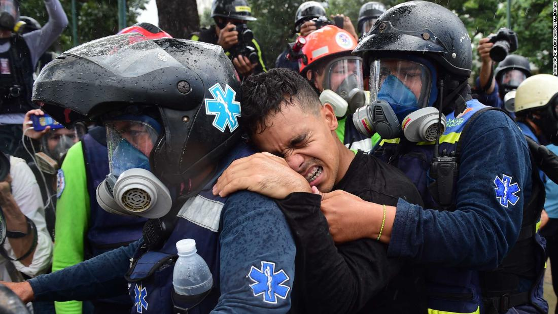 A wounded anti-government demonstrator is helped by medics during clashes with police in Caracas on July 30.