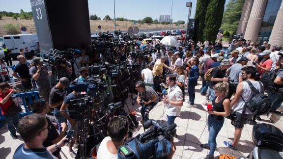Members of the press wait outside the Spanish courthouse in Madrid where he had testified in a case where he is accused of evading taxes