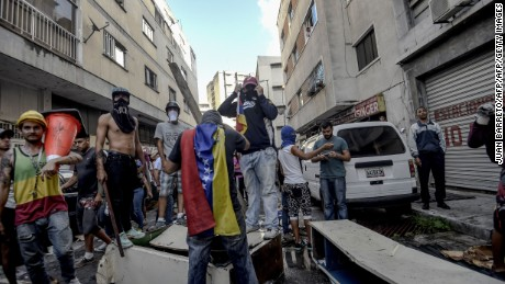 Anti-government activists attack and set on fire a National Traffic Police station during a protest against the election of a Constituent Assembly proposed by Venezuelan President Nicolas Maduro, in Caracas on July 30, 2017. Deadly violence erupted around the controversial vote, with a candidate to the all-powerful body being elected shot dead and troops firing weapons to clear protesters in Caracas and elsewhere. / AFP PHOTO / JUAN BARRETO        (Photo credit should read JUAN BARRETO/AFP/Getty Images)