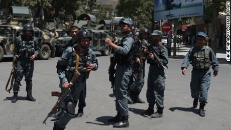 Afghan police officers arrive at the site of a suicide blast in Kabul on July 31.