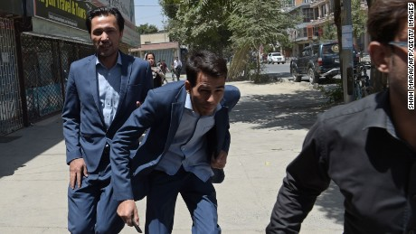 Afghan residents run at the site of a suicide blast near Iraq's embassy in Kabul on July 31.