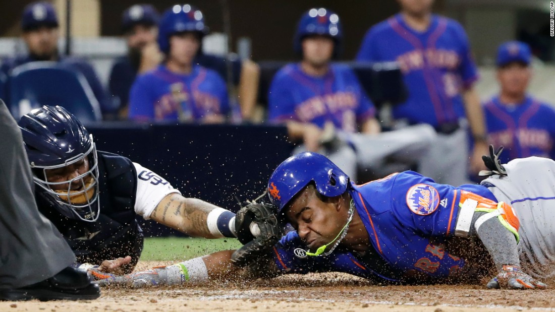 New York Mets outfielder Yoenis Cespedes slides into home plate, beating the tag from San Diego catcher Hector Sanchez during a Major League Baseball game on Tuesday, July 25.