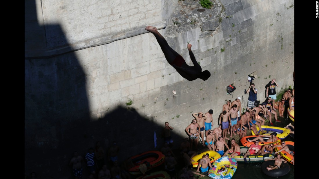 Spectators watch a diver jump from the Old Mostar Bridge in Mostar, Bosnia-Herzegovina, on Sunday, July 30. The high-diving competition in Mostar is more than 400 years old.