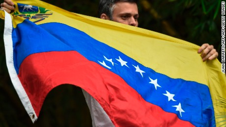 "Venezuelan opposition leader Leopoldo Lopez displays the Venezuelan national flag as he greets supporters gathering outside his house in Caracas, after he was released from prison and placed under house arrest for health reasons, on July 8, 2017. Venezuela's Supreme Court confirmed on its Twitter account it had ordered Lopez to be moved to house arrest, calling it a ""humanitarian measure"" granted on July 7 by the court's president Maikel Moreno. ""Leopoldo Lopez is at his home in Caracas with (wife) Lilian and his children,"" Lopez's Spanish lawyer Javier Cremades said in Madrid. ""He is not yet free but under house arrest. He was released at dawn."" / AFP PHOTO / Juan BARRETO        (Photo credit should read JUAN BARRETO/AFP/Getty Images)"