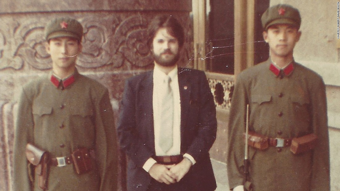 Booth stands between two Chinese soldiers of the People's Liberation Army outside Beijing's Great Hall of the People in 1981.