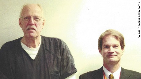 "Retired US State Department counterintelligence officer Robert David Booth, right, stands beside convicted American spy Kendall Myers in 2009. Myers, a former State Department officer, was convicted and sentenced to life in prison for giving US secrets to Cuba. ""This a very rare photo,"" Booth said. Myers was being debriefed at the FBI field office in Washington about his crimes a few months after his arrest. FBI agents don't take photos during espionage debriefings, Booth said. Booth said he would often bring Myers hot pastrami sandwiches and carrot cake to entice him to reveal more information during their questionging sessions. ""I probably got about 70%"" of what I wanted,"" Booth said."