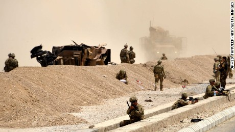US soldiers keep watch near the wreckage of their vehicle in Kandahar on Wednesday.