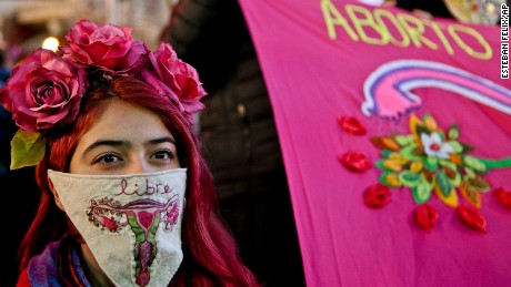 "A woman wearing a handkerchief with an embroidered uterus and the Spanish word for ""free"", takes part in a march in favor of a bill backed by President Michelle Bachelet, to legalize abortions in three situations: when the mother's life is in danger, when the fetus is not viable, and in cases of rape, in Santiago, Chile, Tuesday, July 25, 2017. (AP Photo/Esteban Felix)"