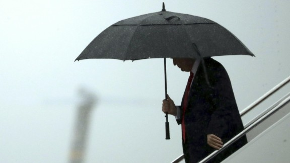 U.S. President Donald Trump holds an umbrella after stepping out of Air Force One in Joint Base Andrews, Maryland, U.S., on Friday, July 28, 2017. Trump replaced his chief of staff Reince Priebus today announcing on Twitter that he had appointed Homeland Security Secretary John Kelly to the job. Photographer: Chip Somodevilla/Pool via Bloomberg