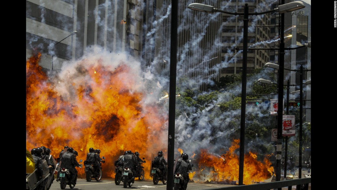 "Members of Venezuela's national police are caught in an explosion Sunday, July 30, as they ride motorcycles near Altamira Square in Caracas, Venezuela. <a href=""http://www.cnn.com/2017/07/30/americas/venezuela-on-edge-vote/index.html"" target=""_blank"">Police and protesters clashed</a> during a controversial vote to elect a special assembly with powers to rewrite the constitution."
