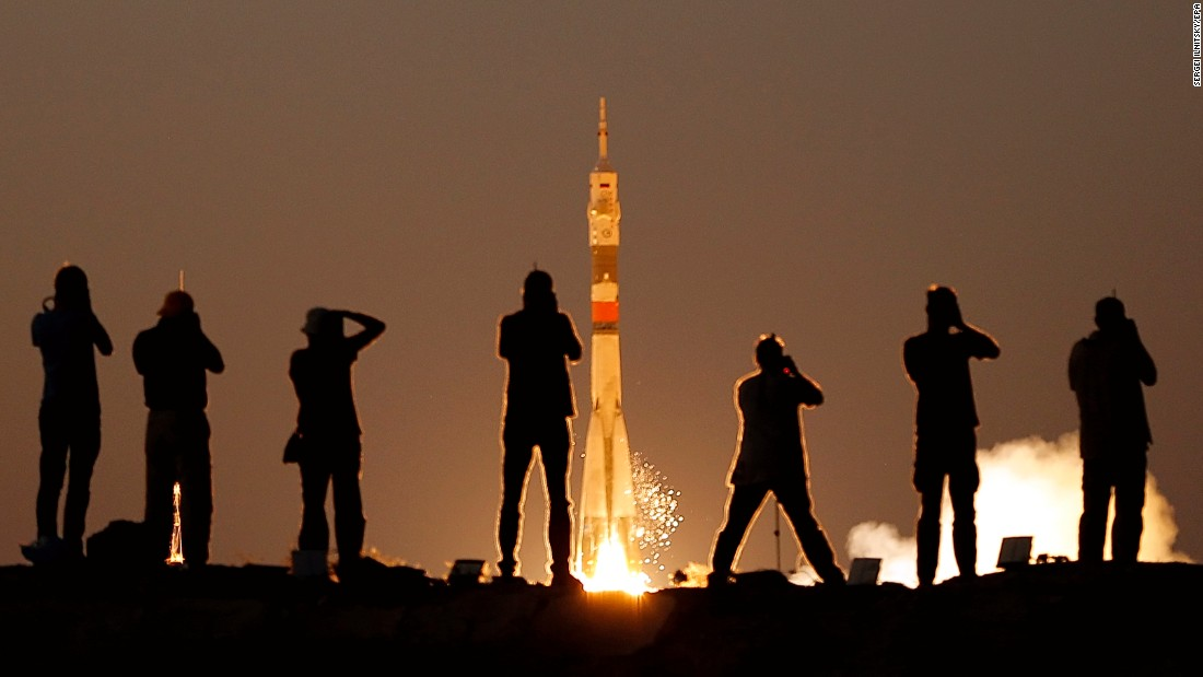 Photographers take pictures of a rocket as it carries three men to the International Space Station on Friday, July 28. The rocket was launched from the Baikonur Cosmodrome in Kazakhstan.