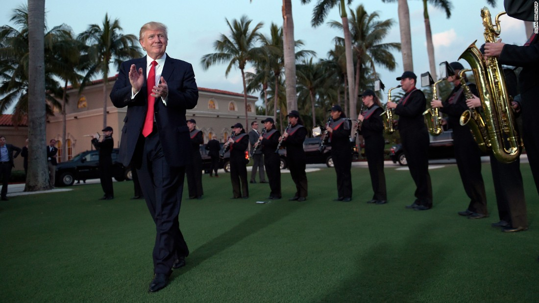 President Donald Trump listens to a high school marching band as he arrives at the Trump International Golf Club in West Palm Beach, Florida, in February 2017. He and the first lady were spending a weekend away from the White House. Here's a look at how Trump and other US presidents have escaped the pressures of the Oval Office.