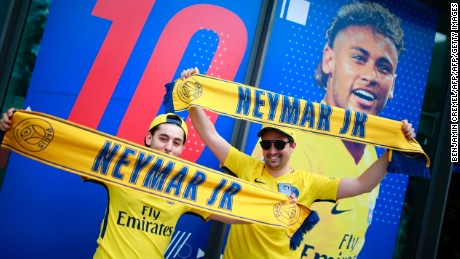 Supporters of Paris-Saint-Germain's new signing Neymar pose with scarves outside the Paris-Saint-Germain (PSG) football club store on the Champs Elysees avenue in Paris on August 4