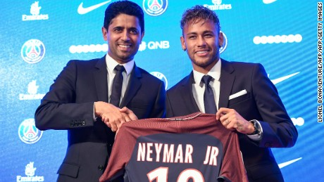 Neymar (R) poses with his jersey next to Paris Saint Germain's (PSG) Qatari president Nasser Al-Khelaifi during a press conference on August 4, 2017.