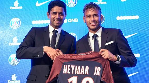 Neymar (R) poses with his jersey next to Paris Saint Germain