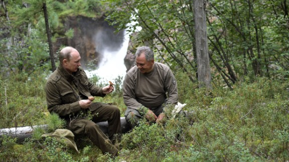 Russian President Vladimir Putin, left, shows mushrooms to Defense Minister Sergei Shoigu during his vacation this week in the remote Tuva region of southern Siberia.