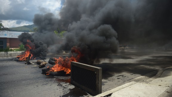 "A barricade set by anti-government activists burns in flamesin Venezuela's third city, Valencia, on August 6, 2016, a day after a new assembly with supreme powers and loyal to President Nicolas Maduro started functioning in the country. In the video posted online earlier, allegedly at an army base used by the National Bolivarian Armed Forces in Valencia, a man presenting himself as an army captain declared a ""legitimate rebellion... to reject the murderous tyranny of Nicolas Maduro"" and demanded a transitional government and ""free elections."" After the video surfaced, military chiefs said troops had put down the ""terrorist"" attack."