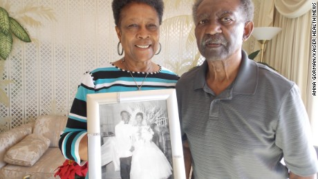 Dorothy and Levi Reeves stand in their Oakland, Calif., home, holding their wedding photo from 57 years ago. Dorothy Reeves, 79, agreed to donate both of their brains after death to the University of California-Davis for research.  (Anna Gorman/KHN)