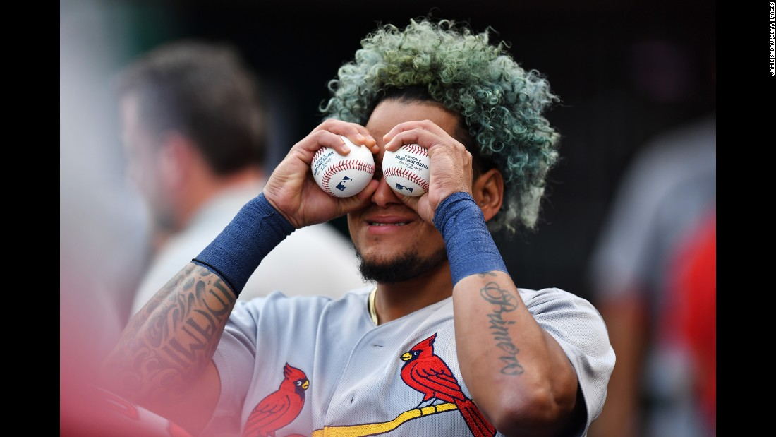 St. Louis pitcher Carlos Martinez turns a pair of baseballs into binoculars as he fools around in the dugout on Saturday, August 5.