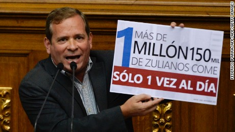 "Opposition deputy Juan Pablo Guanipa (front) displays a placard that reads: ""More than 1 million 150 thousand zulians eat just once a day""  in front of the President of the National Assembly Henry Ramos Allup, during a session in Caracas, on December 13, 2016. / AFP / FEDERICO PARRA        (Photo credit should read FEDERICO PARRA/AFP/Getty Images)"