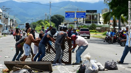 "Anti-government activists set up a barricade in the streets of Venezuela's third city, Valencia, on August 6, 2017, a day after a new assembly with supreme powers and loyal to President Nicolas Maduro started functioning in the country. In the video posted online earlier, allegedly at an army base used by the National Bolivarian Armed Forces in Valencia, a man presenting himself as an army captain declared a ""legitimate rebellion... to reject the murderous tyranny of Nicolas Maduro"" and demanded a transitional government and ""free elections."" After the video surfaced, military chiefs said troops had put down the ""terrorist"" attack.   / AFP PHOTO / Ronaldo SCHEMIDT        (Photo credit should read RONALDO SCHEMIDT/AFP/Getty Images)"