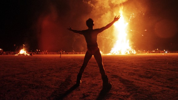 "A ""Burning Man"" participant holds up his arms as the wooden man effigy is burned at the conclusion of an earlier ""Burning Man Festival"" in Nevada's Black Rock Desert. More than 15,000 people congregated at this man-made town in the desert to celebrate radical, creative self-expression."