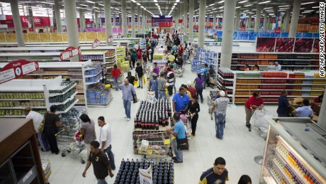 Consumers during the inauguration of the state-owned Bicentenario supermarket in Caracas, on June 4, 2013. For almost a month there has been a shortage around the country of toilet paper due to a drop in its production and imports. AFP PHOTO/Leo RAMIREZ        (Photo credit should read LEO RAMIREZ/AFP/Getty Images)