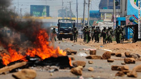 Kenyan security personnel walk towards burning barricades on a road in Kisumu on Wednesday.