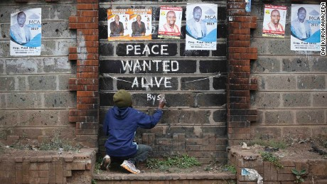 Street artist Solomon Muyundo, also known as Solo7, paints a message of peace on the wall in Kibera slum, one of Odinga's strongholds in the capital Nairobi on Wednesday.