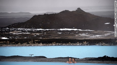 People pose for a 'selfie' as they swim in hot springs on April 12, 2017 in Myvatn, Iceland.  / AFP PHOTO / LOIC VENANCE        (Photo credit should read LOIC VENANCE/AFP/Getty Images)