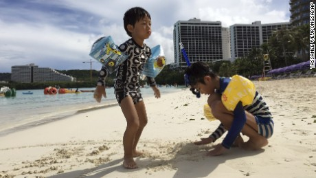 Children play in the sand in Tumon, Guam, on Thursday, August 10.