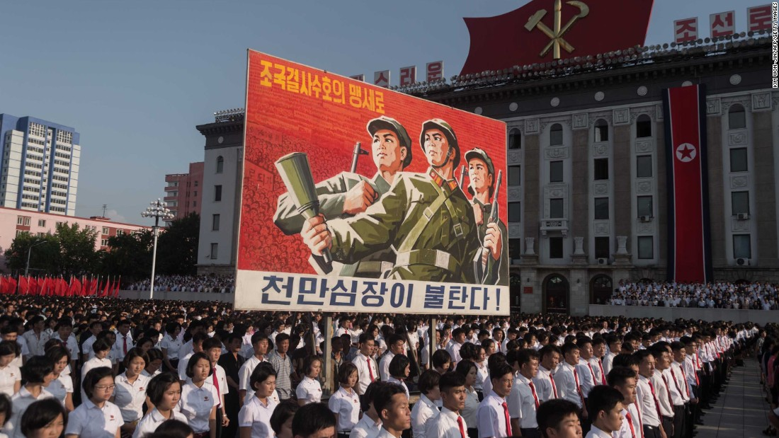 "People in Pyongyang, North Korea, attend a rally Wednesday, August 9, in the capital's Kim Il Sung Square. The rally showed support for the North Korean government and its bellicose stance against the United States. The sign here reads ""protect our nation to the death"" and ""hearts of 10 million people are burning."""