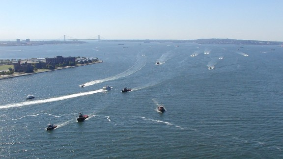 The view south from Manhattan shows tugs racing from Staten Island and New Jersey to the Battery. On the left is the southern tip of Governors Island. The Verrazano-Narrows Bridge is visible in the background.