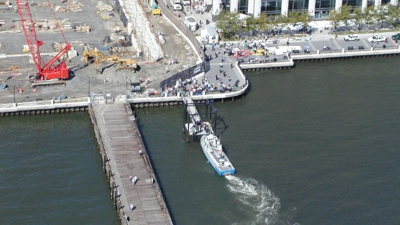 Passengers disembark just north of Paulus Hook in Jersey City. A ferry terminal receives smaller ferryboats and NYPD vessels, while larger boats, including Fireboat John D. McKean, drop their passengers at the abandoned wooden pier on the left. On the shore, EMTs have begun laying out color-coded tarps to tend to the injured in their makeshift triage center.