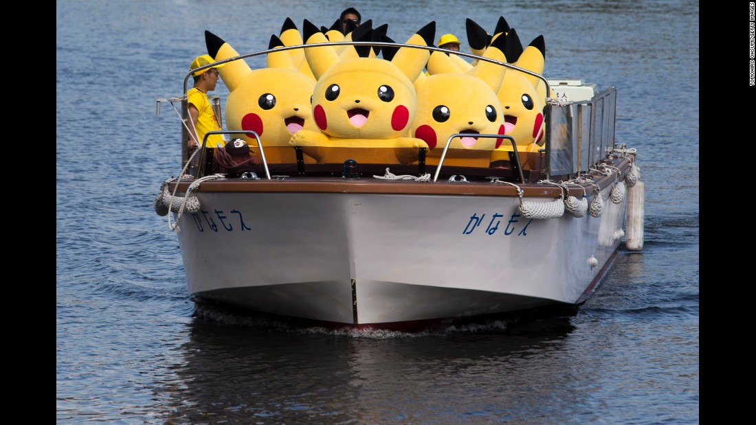 "Performers dressed as Pikachu, a character from the ""Pokemon"" franchise, ride on a boat during the Pikachu Outbreak event in Yokohama, Japan, on Wednesday, August 9. Hundreds of Pikachus are appearing at city landmarks to attract visitors and tourists through August 15."
